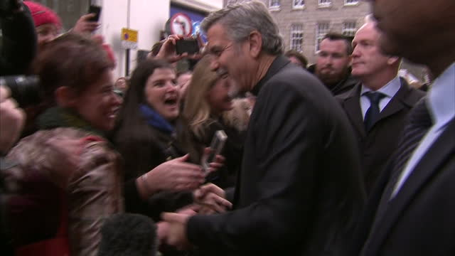 Shows Exterior Shots George Clooney actor arriving outside sandwich shop and shaking hands with large crowds of fans including women who can't...