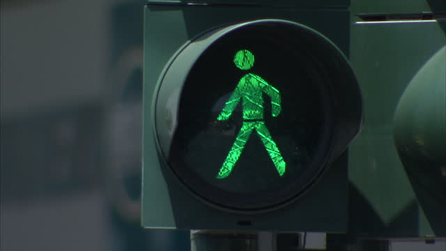 Shows exterior shots green man on pedestrian light people walking along the pavement on July 22 2015 in Athens Greece