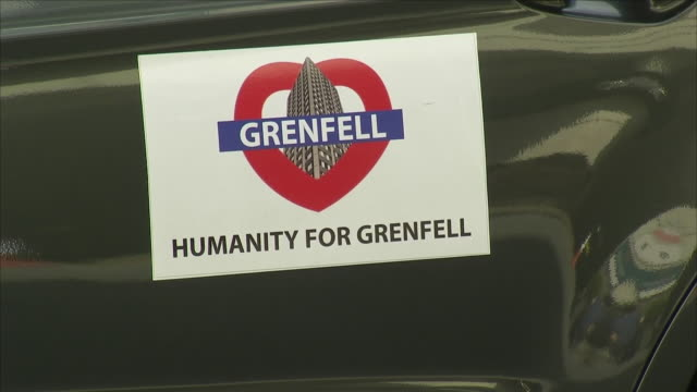 Shows exterior shots 'Humanity for Grenfell' signs on side of car outside building where opening day of the Phase 1 Grenfell Inquiry hearings are...
