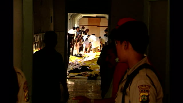 Shows exterior shots ice being delivered to morgue for victims of the Bali bombings and officials standing in entrance way to building in Kuta on...