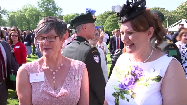 shows exterior shots interview with guests speaking on meeting new duke and duchess of sussex at an official buckingham palace summer garden party to... - buckingham palace stock-videos und b-roll-filmmaterial