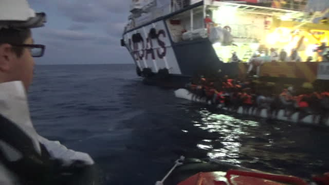stockvideo's en b-roll-footage met shows exterior shots large group of migrants desperately sat on top of an unsuitable inflatible boat shouting and in distress as rescuers try to help... - red sea
