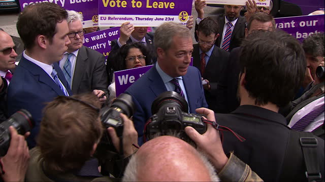 shows exterior shots leader of ukip nigel farage standing in middle of media scrum giving interview to reporter with ukip supporters from bus holding... - スクラム点の映像素材/bロール