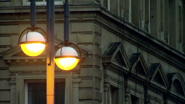 vidéos et rushes de shows exterior shots lights on lamppost shining brightly with bus driving past along road, in late afternoon on rainy winter's day on december 09,... - éclairage public