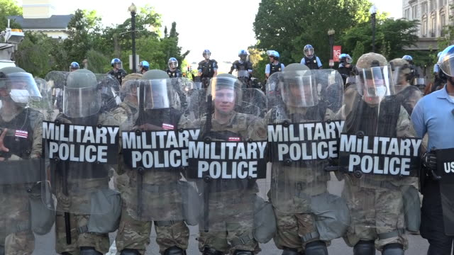 stockvideo's en b-roll-footage met shows exterior shots line of peaceful protesters standing in front of line of military police with riot shields locked in wall, protesting over death... - mp