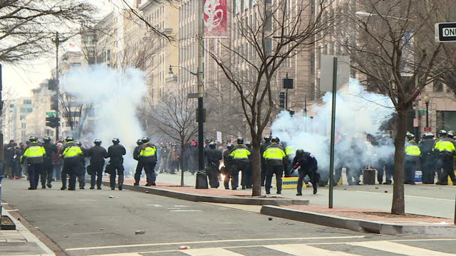 shows exterior shots line of riot police across road in front of group of protesters stun and concussion grenades letting off smoke and bangs as... - inauguration into office stock videos & royalty-free footage