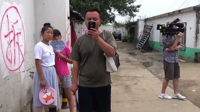shows exterior shots local chinese resident filming on his mobile phone as reporter and cameraman film in his neighbourhood on 16th august 2017 in... - lavoratore emigrante video stock e b–roll