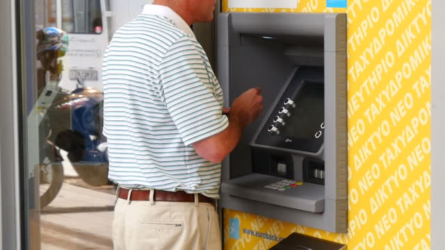 shows exterior shots man using cash machine at branch of national bank another using atm at eurobank branch on june 28 2015 in athens greece - panathinaiko stadium stock videos & royalty-free footage