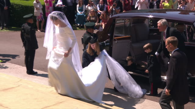 vídeos y material grabado en eventos de stock de shows exterior shots meghan markle arriving at st george's chapel in windsor castle, getting out of car, waving to crowd and walking up steps to the... - 2018