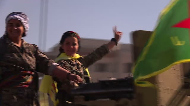 Shows exterior shots members of the Women's Brigade unit of the YPG celebrating in the central square in Raqqa following the defeat of ISIS in their...