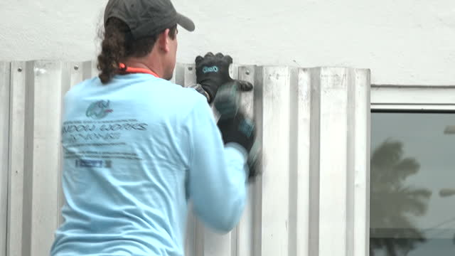 shows exterior shots men putting up steel shutters over shop windows as they prepare properties for arrival of hurricane maria puerto rico's governor... - shutter stock videos & royalty-free footage