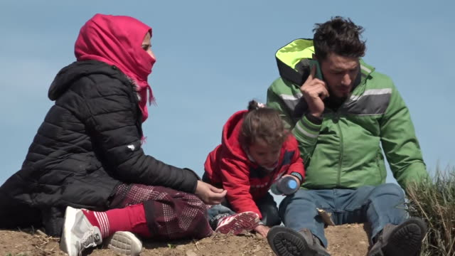 shows exterior shots migrant and refugee children playing as their families sitting in dirt near banks of river close to the border between turkey... - problems stock videos & royalty-free footage
