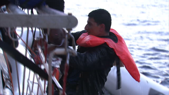 Shows exterior shots migrant being pulled aboard the Migrant Offshore Aid Station vessel after ending up in the sea during a rescue attempt where the...
