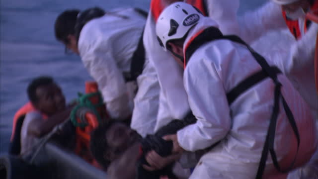 stockvideo's en b-roll-footage met shows exterior shots migrant offshore aid station rescue worker saving migrants in the sea, pulling them over to the fast response small boat to be... - red sea