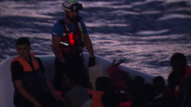stockvideo's en b-roll-footage met shows exterior shots migrants crowded in inflatable boat with fast response rescue boat nearby, and moas rescuer sitting in prow of migrants boat... - red sea