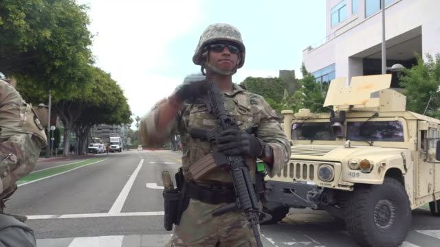 """shows exterior shots military vehicles on streets and armed soldiers on patrol in los angeles, california. """"is this who we are? is this who we want... - armed police forces stock videos & royalty-free footage"""