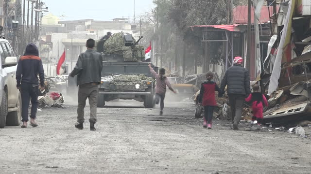 Shows exterior shots Mosul residents including children trapped in the city by the fighting between ISIS and Iraqi forces and Iraqi forces vehicles...