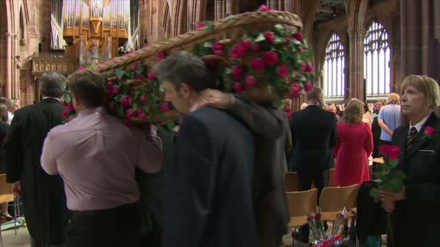 voiced shows exterior shots mourners gathered outside and arriving at manchester cathedral holding roses for funeral of saffie roussos exterior and... - godmother stock videos & royalty-free footage