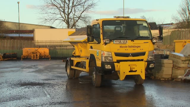 Shows exterior shots names on the front of various road gritting lorries at salt depot including 'Brad Grit' 'Nicole Saltslinger' and 'Basil Salty'...