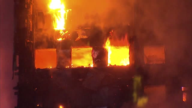 vidéos et rushes de shows exterior shots night shots close up flames growing as fires burn and clouds of smoke across upper floors of grenfell tower block in west london... - brasier