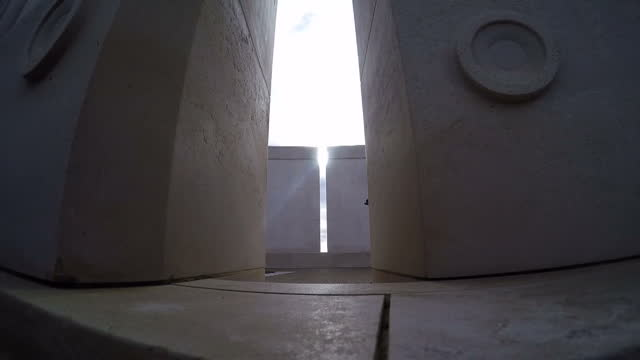 Shows Exterior shots of sun shining through columns of the War Memorial at the National Memorial Arboretum in Staffordshire UK to commemorate...