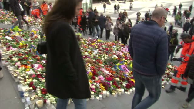 shows exterior shots pan across flowers and tributes to victims of terror attack as people look at them on 9th april 2017 in stockholm sweden - temporäre gedenkstätte stock-videos und b-roll-filmmaterial