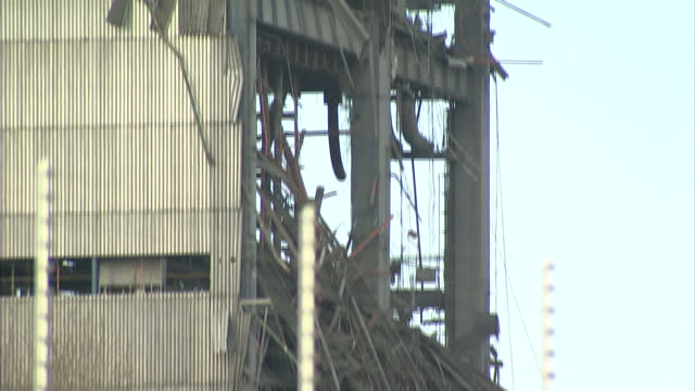 shows exterior shots pan down the outside of standing part of collapsed building at didcot power station with twisted metal and wreckage from... - didcot stock videos and b-roll footage