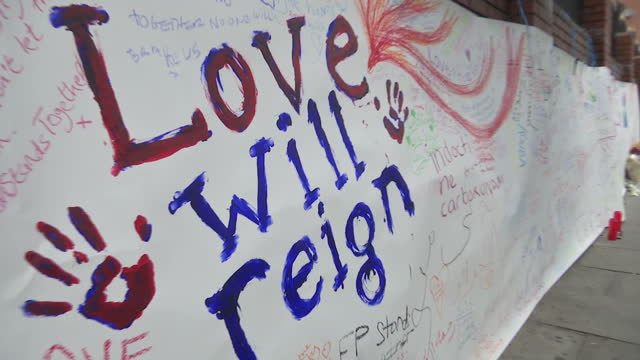 Shows exterior shots pans along messages of support written on paper along wall near scene of terror attack in Finsbury Park People across faiths...
