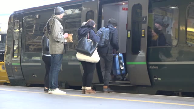 shows exterior shots passengers lining up to board trains and stepping on board train. rail passengers are being urged to check before they travel as... - passenger stock videos & royalty-free footage