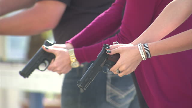 Shows exterior shots people at a gun range drawing guns firing at targets before putting handguns back in their holster on October 16 2014 in Salt...