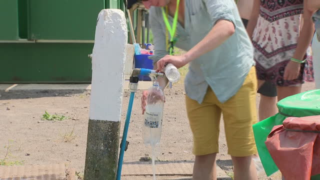Shows exterior shots people at Glastonbury Festival filling water bottles and containers at taps and carrying water through campsite on hot day on...