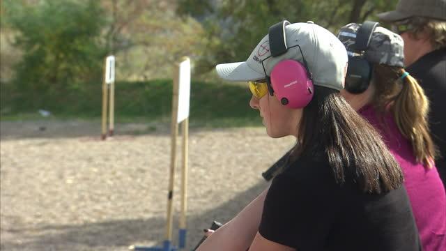 Shows exterior shots people at gun range firing handguns at targets on October 16 2014 in Salt Lake City UT