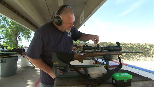 Shows exterior shots people at gun range firing rifles at targets on October 16 2014 in Salt Lake City UT