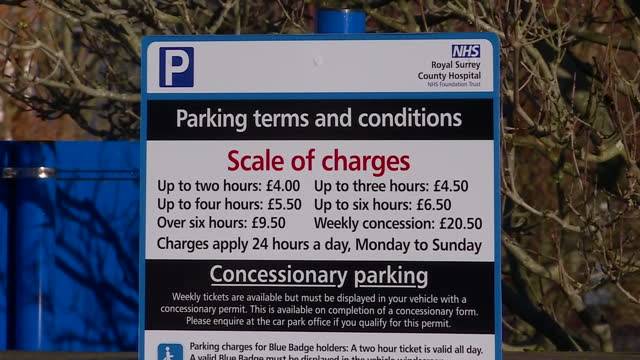 Shows exterior shots people buying parking tickets from machine in car park and parking charge signs Exterior cars driving through and parking in car...
