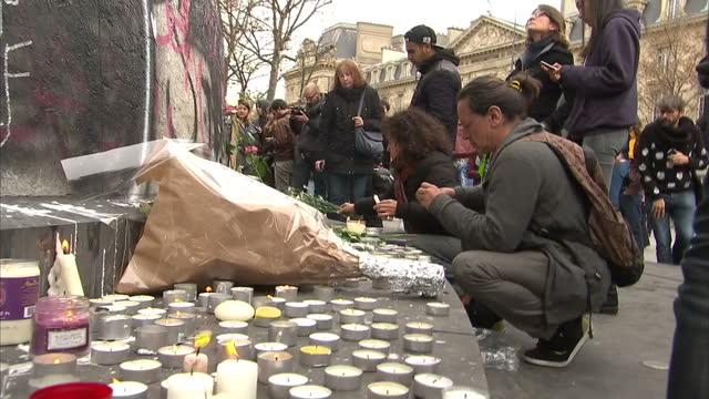 vidéos et rushes de shows exterior shots people gathered near base of monument in place de la republique in paris, lighting candles and looking at tributes left to... - victime