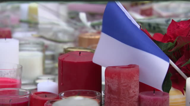 shows exterior shots people looking at tributes left to victims of the strasbourg christmas market shooting and lighting candles police in the french... - 仮設追悼施設点の映像素材/bロール