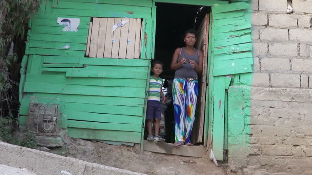 shows exterior shots people outside houses in slums in turbaco including girl with face mask over mouth. the number of zika cases in colombia is... - virus zika video stock e b–roll