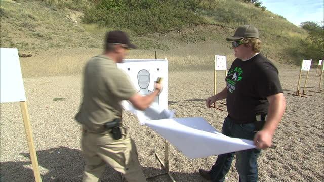 Shows exterior shots people putting up targets at a gun range on October 16 2014 in Salt Lake City UT