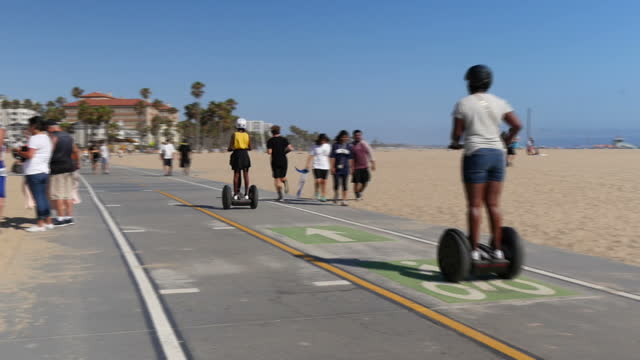 vidéos et rushes de shows exterior shots people riding segways along track across santa monica beach on 26th july 2017 in california usa - santa monica