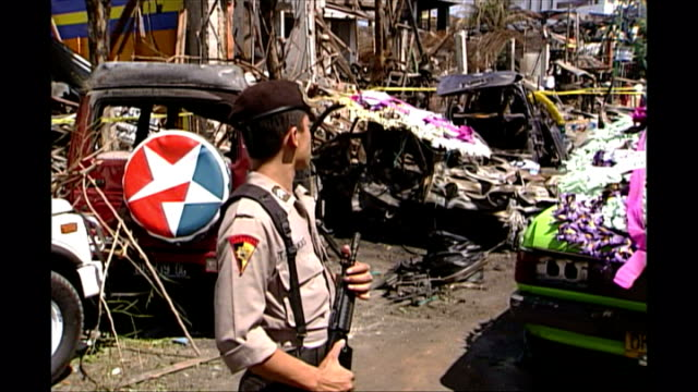 shows exterior shots people standing behind police tape at scene of bali bombings in kuta flowers and elaborate floral tributes arriving and being... - monumento commemorativo temporaneo video stock e b–roll