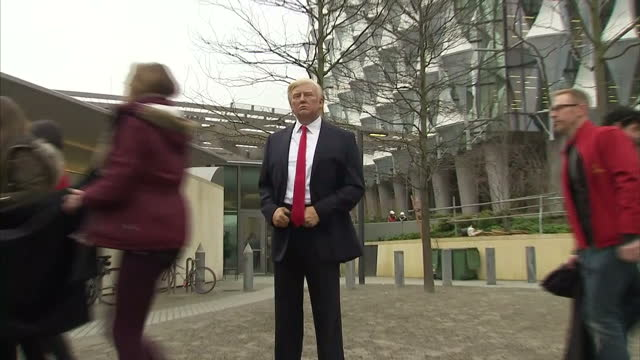 Shows exterior shots people unveiling waxwork of US President Donald Trump outside the new US Embassy in Nine Elms London and people taking photos of...
