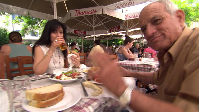 shows exterior shots people walking in pedestrian area two people sat enjoying their food on june 28 2015 in athens greece - panathinaiko stadium stock videos & royalty-free footage