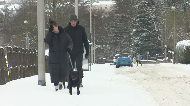 shows exterior shots people walking their dog in snow in edinburgh, scotland. the lowest uk temperature for more than a decade was recorded in the... - winter stock videos & royalty-free footage