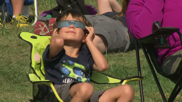 shows exterior shots people wearing reflecting and protective glasses looking up to the sky watching the total solar eclipse on 21st august 2017 in... - solar eclipse glasses stock videos and b-roll footage