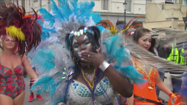 VOICED Shows exterior shots performers in costumes arriving and attending the Notting Hill Carnival Exterior shots firefighters and other members of...