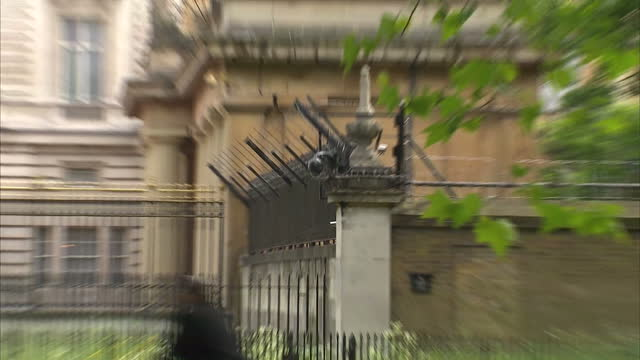 shows exterior shots perimeter wall surrounding grounds of buckingham palace in london, with security cameras monitoring road and spiked railings and... - surrounding wall点の映像素材/bロール