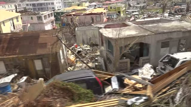 vídeos de stock, filmes e b-roll de shows exterior shots point of view tracking shots past piles of debris and damaged building and properties with people starting to clean up in... - 2017