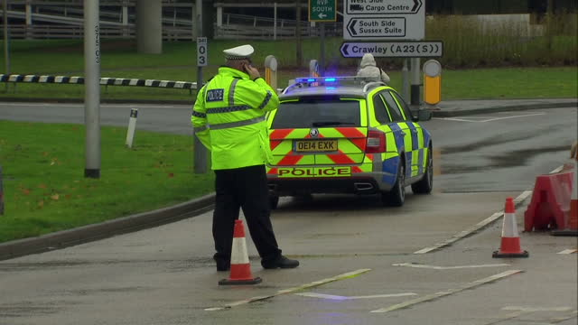 shows exterior shots police officers and security personnel directing traffic around gatwick airport in the uk following secuirty alert exterior... - directing stock videos and b-roll footage