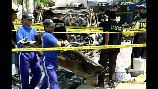 Shows exterior shots police officers forensics teams and investigators at the scene of the Bali bombings in Kuta sifting through the debris and...