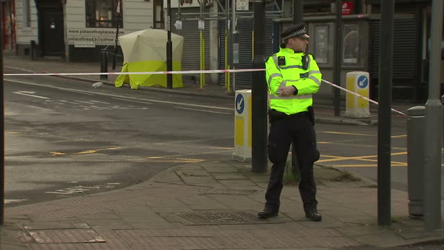 shows exterior shots police officers standing at police cordon around stabbing crimes scene in tulse hill in london and forensics tent over site of... - messerstecherei stock-videos und b-roll-filmmaterial